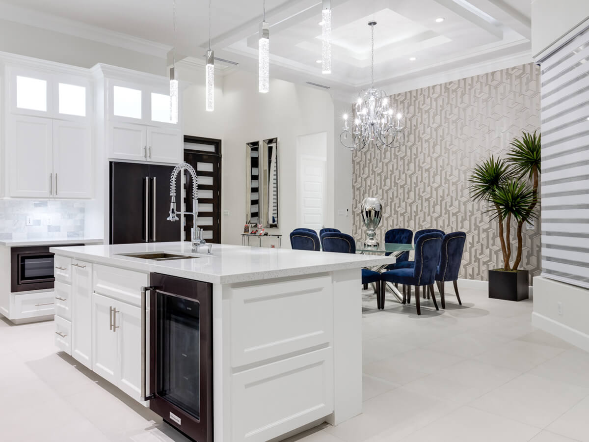 View of a custom built white kitchen and living room, designed by Dolcan Homes