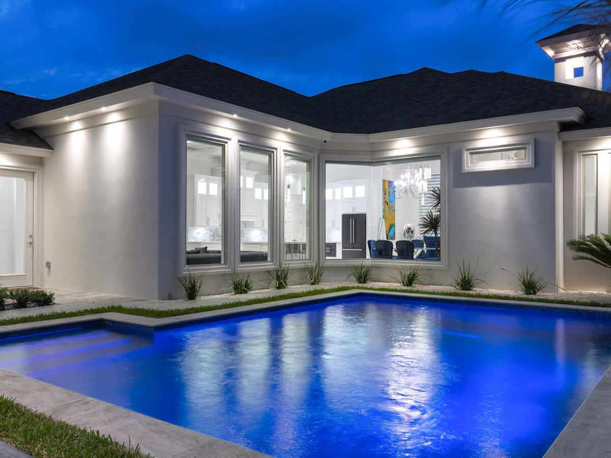White home with pool and garden