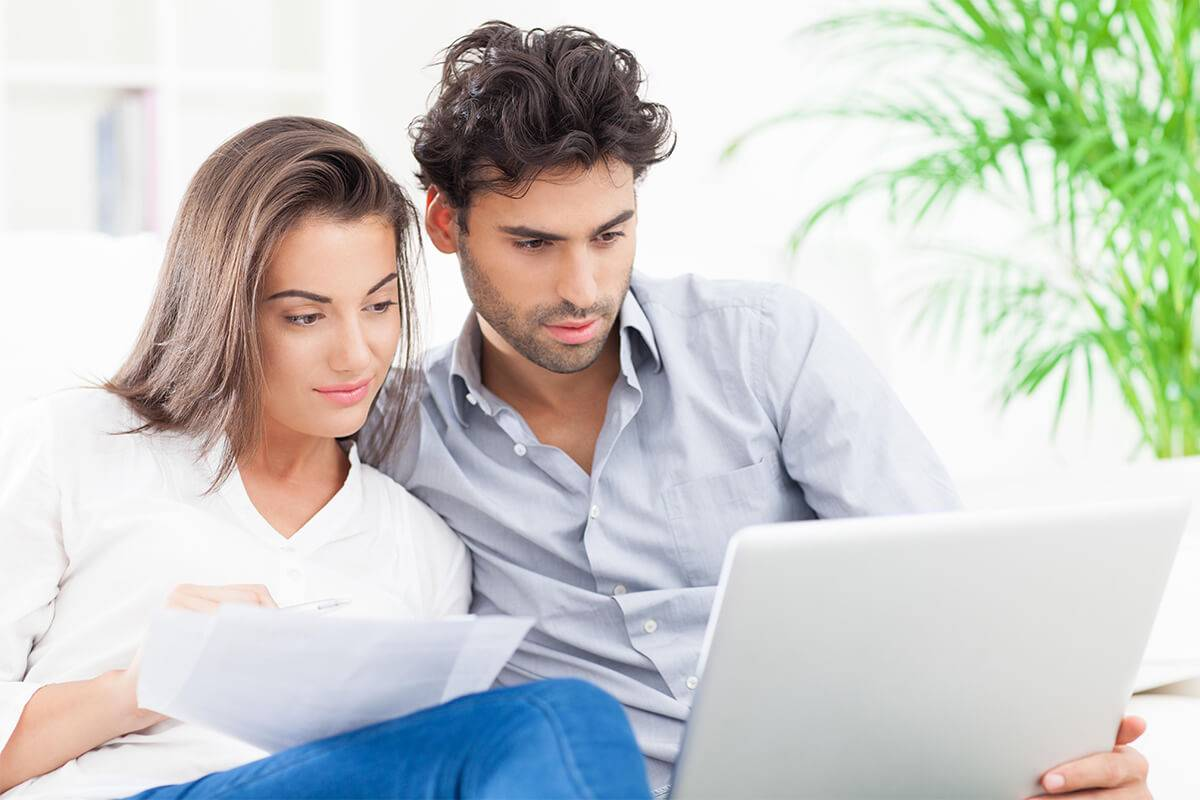 Couple in front of laptop doing home buying research