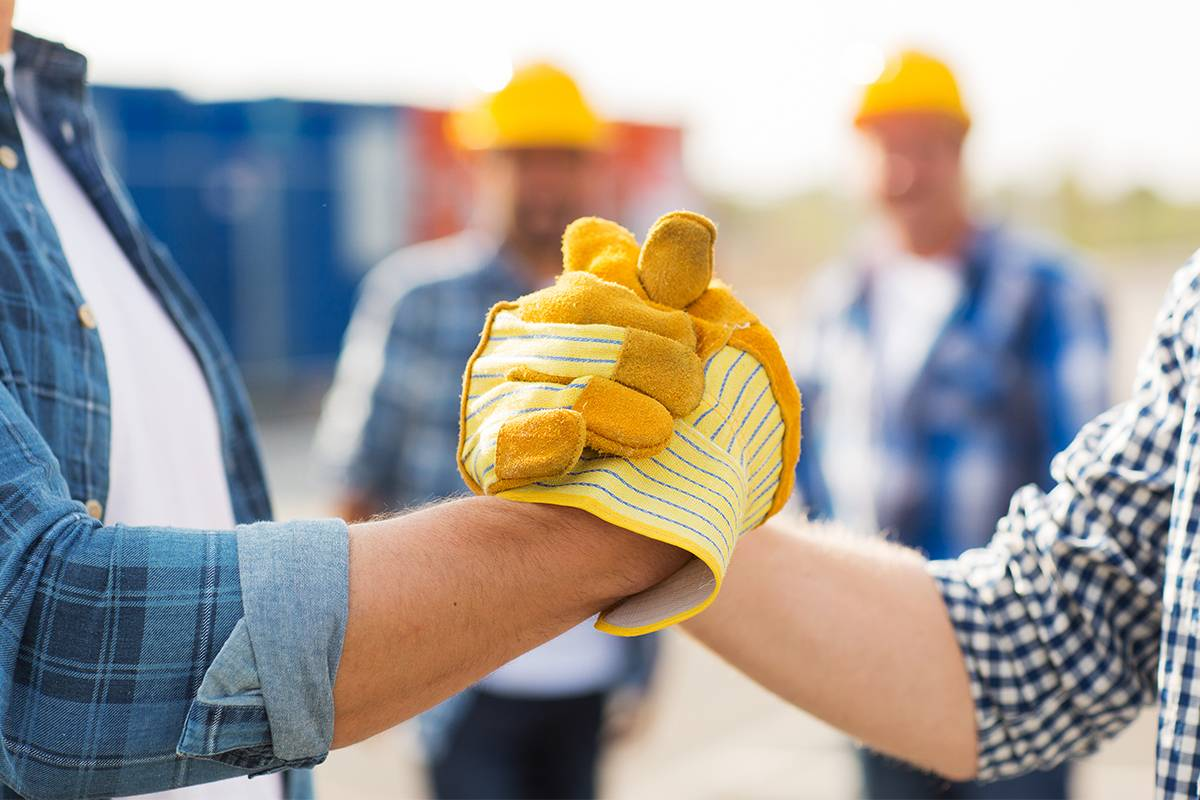 Close up of builders with gloves shaking hands
