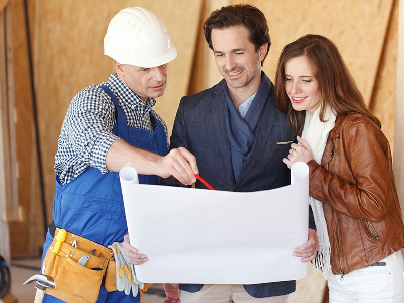 Man and woman couple talking to contractor holding plan