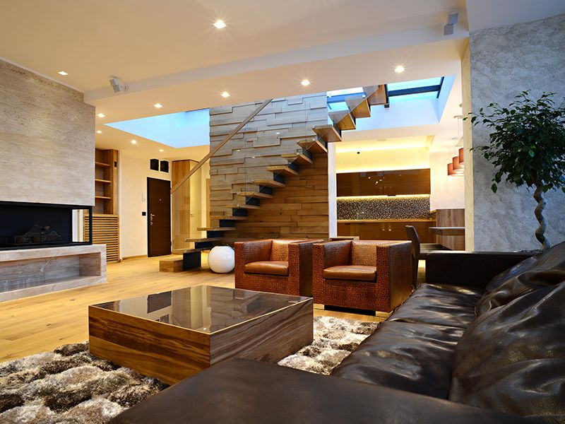 Luxury living room interior with stairs and mixed materials in walls
